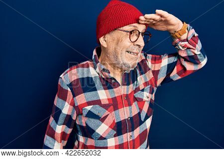Handsome mature man wearing hipster look with wool cap very happy and smiling looking far away with hand over head. searching concept.