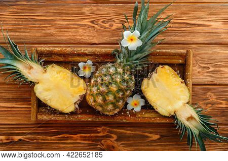 Ripe Pineapple. Tropical Summer Fruit Pineapple Halves And Whole Pineapple On Brown Dark Table In Wo