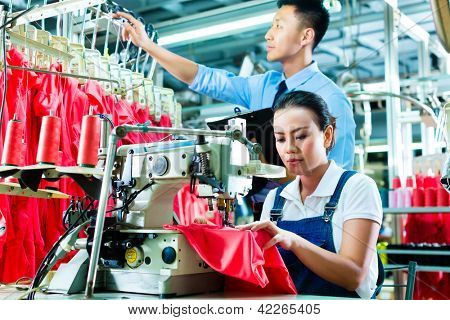 Seamstress or worker in a factory sewing with a sewing machine, a foreman checks the yarn