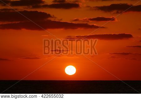 The Sun Sets Over The Horizon Against The Fiery Red Illumination Of The Sky.