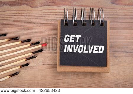 Get Involved. Burnt Matches And Notebook On A Wooden Background