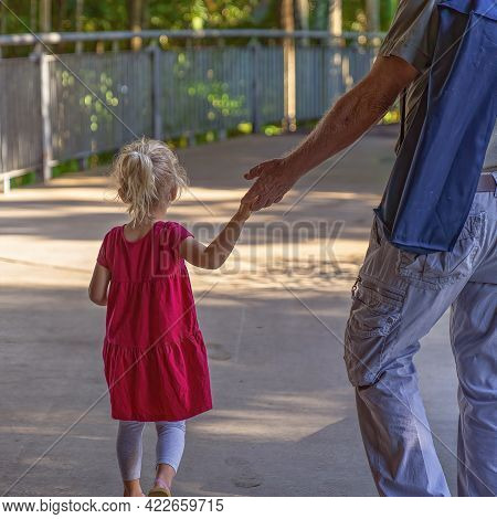 Mackay, Queensland, Australia - June 2021: Young Girl Holding Her Grandfather's Hand As She Goes For