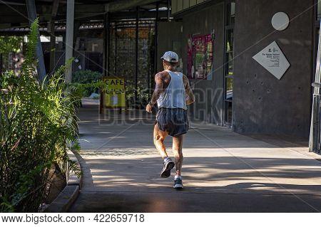 Mackay, Queensland, Australia - June 2021: Male Runner Exercising In The Botanic Gardens Where He Ru