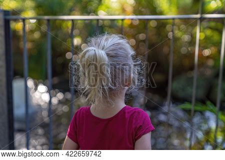 Mackay, Queensland, Australia - June 2021: Close Up Of A Young Girl Looking Through A Fence At The B