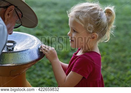Mackay, Queensland, Australia - June 2021: Young Girl Child And Her Grandfather At A Drinking Founta