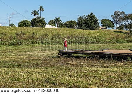Mackay, Queensland, Australia - June 2021: A Small Three Year Old Girl Standing On A Boardwalk Overl