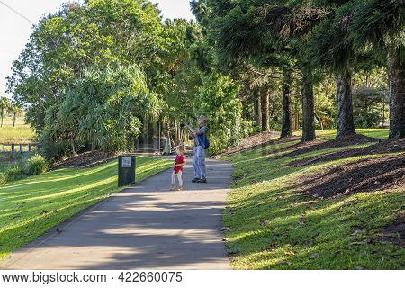 Mackay, Queensland, Australia - June 2021: A Young Child Stands Beside Her Grandfather As He Takes A