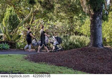 Mackay, Queensland, Australia - June 2021: Two Mothers Push Their Babies In Prams As They Exercise I