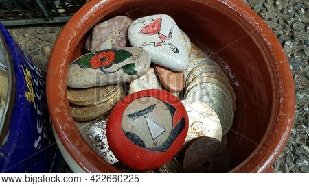 Selective Focus Vintage Drachma Coins And Painted Stones Inside Old Clay Pot At Flea Market In Athen
