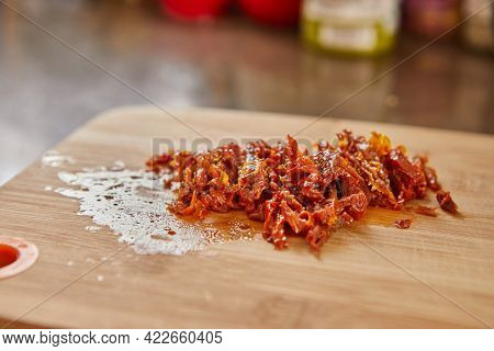 Sun-dried Tomatoes On Wooden Board, Ready For Making Muffins With Sun-dried Tomatoes