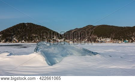 Transparent Glittering Ice Floe In The Middle Of A Frozen And Snow-covered Lake. Sun Glare On The Ed