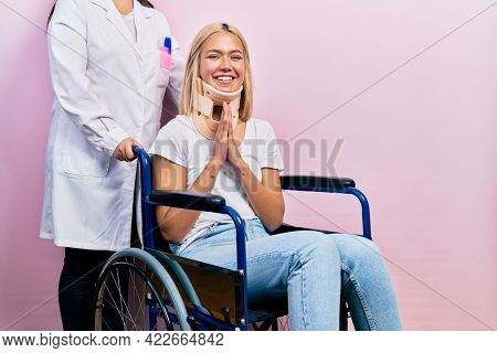 Beautiful blonde woman sitting on wheelchair with collar neck praying with hands together asking for forgiveness smiling confident.