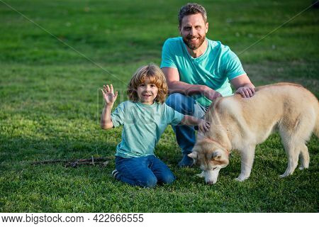 Beautiful Happy Family Is Having Fun With Dog Husky. Happy Father And His Son Playing With Dog In Pa