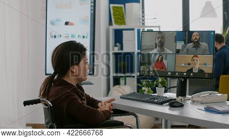 Paralyzed Immobilized Manager Woman Speaking Online With Remotely Coworkers Sitting Wheelchair In St