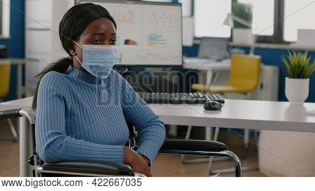 African Invalid Handicapped Woman Employee With Protection Mask Sitting Immobilized Paralized In Whe