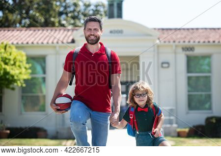 Parent And Pupil Of Primary School Go Hand In Hand. Teacher In T-shirt And Cute Schoolboy With Backp