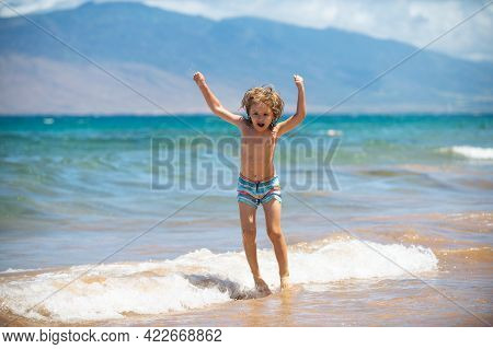 Child Jumping On Ocean Beach. Kid Jumping In The Waves At Sea Vacation. Little Boy Jump On Tropical