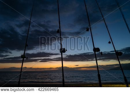 Colorful Sunset With Fishing Rod On Ocean. Silhouette Of People And Fishing Rods.