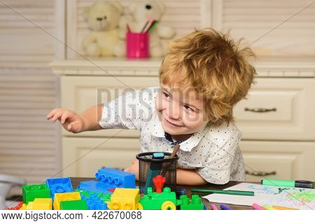 Portrait Of Little Boy Playing With Colorful Blocks In Playroom. Concept Of Kids Face.