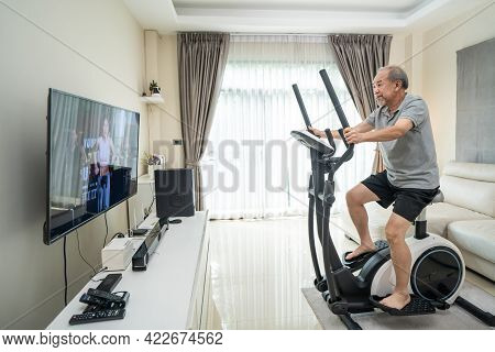 Asian Senior Elderly Man Workout Cardio On Cycling Exercise Bike Machine At Home For Well Being. Act