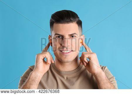 Man Inserting Foam Ear Plugs On Light Blue Background