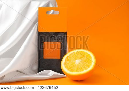 Scented Sachet And Half Of Orange On Color Background