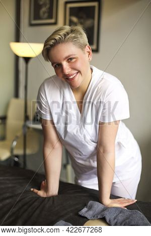 Cheerful Professional Masseuse In White Uniform In Cozy Room In Salon And Looking At Camera