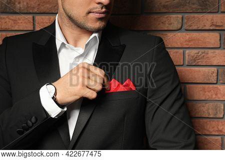 Man Fixing Handkerchief In Breast Pocket Of His Suit Near Brick Wall, Closeup