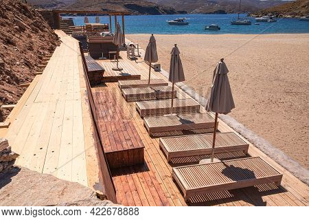 Sunbeds And Umbrellas On The Kolona Beach At Kythnos, Greece In The Morning At The Beginning Of The