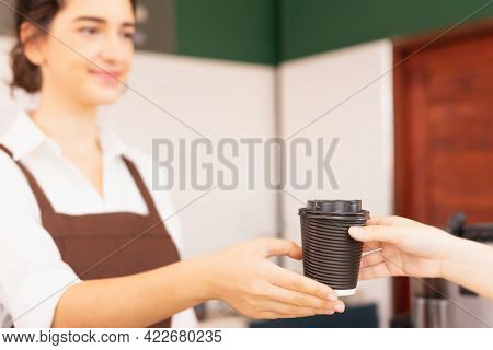 Left Side View Of Beautiful Caucasian Barista Woman Happy To Give Takeaway Coffee Cup To Customer An