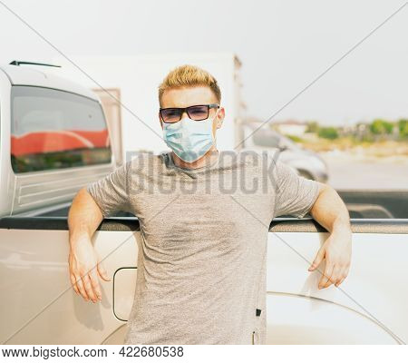 White Caucasian Wear Virus Facemask And Stand With Placing Arms On Car While Waiting For Filling Hig