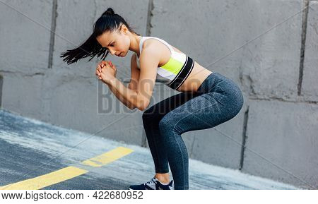 Sporty Woman Doing Squat Exercises Outdoors. Fit Female In Modern Sportswear Exercising Outside On T