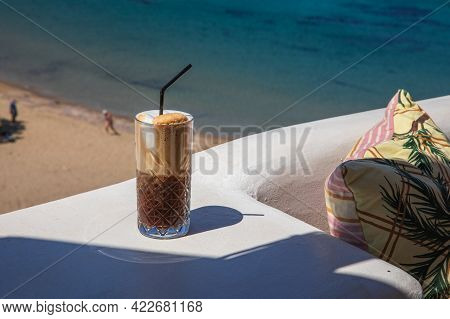 Glass Of Yummy Iced Coffee Or Greek Freddo Cappuccino On The Seascape Background On A Summer Sunny D