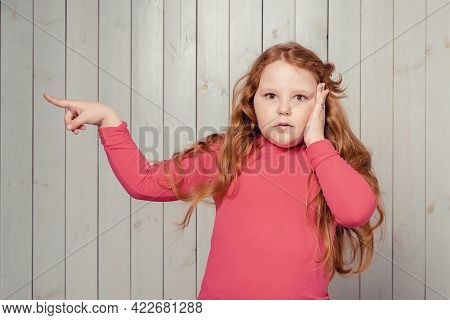 Surprised And Excited Redhead Preteen Girl Pointing Aside, Showing Something Interesting With Amazed