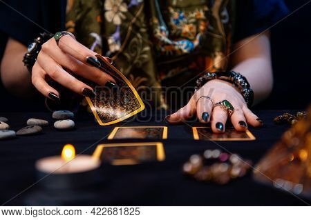 Cartomancy. Fortune-telling On Cards. A Fortune Teller Lays Out Tarot Cards. Close Up Of Hands. The