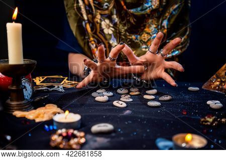 Female Hands Of A Fortune Teller Read Runes. Tarot Cards, Jewels And Candles Are On The Table. The C