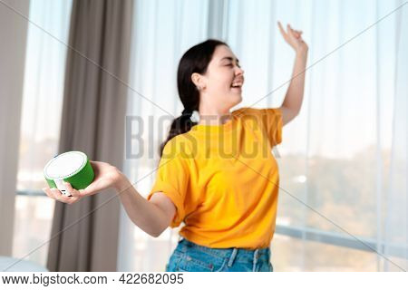 Portrait Of A Young Girl Holding A Portable Smart Speaker That Plays Music And Dances. The Concept O