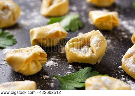 Uncooked Pelmeni Dumplings On Black Background. Close Up