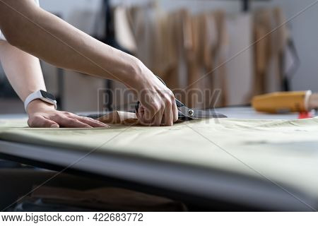 Tailor Hand Hold Scissors Cut Fabric Material For Sewing. Closeup Of Work Process Of Clothes Creatio