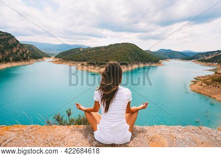 Healthy Young Woman In White Clothes Meditating Or Practicing Yoga In The Nature. Woman Sitting In Y