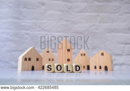 Miniature House And Wooden Blocks With The Word Sold On Marble Table.real Estate Concept.rent Apartm