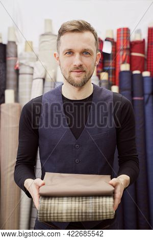 Elegant Caucasian Man Tailor In Black T-shirt And Vest Holds Folded Stack Of Brown And Tweed Textile