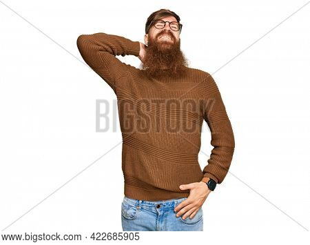Young irish redhead man wearing casual clothes and glasses suffering of neck ache injury, touching neck with hand, muscular pain