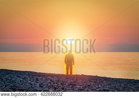 Silhouette Of A Man Stands On The Seashore In The Light Of Sunset Sun.  Search For God Concept. Defo