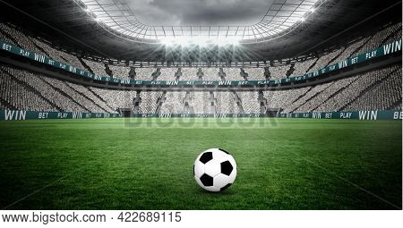 Composition of football on football pitch with spotlights in sports stadium. championships, sports and competition concept digitally generated image.