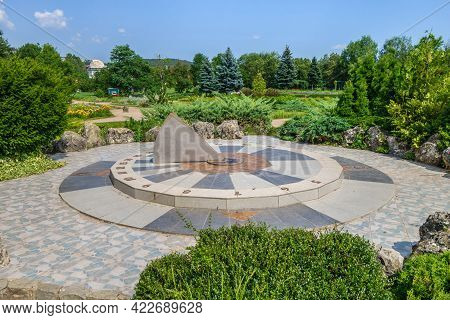 Old Sundial Showing Time And Sides Of The World. Large Dial Surrounded By Decorative Stones And Bloo