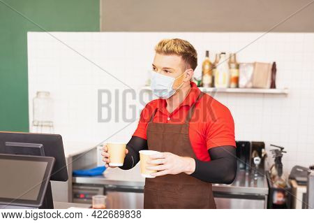 White Caucasian Barista Man Holds Two Coffee Cups After Making Coffee At Coffee Bar. Barista Work At