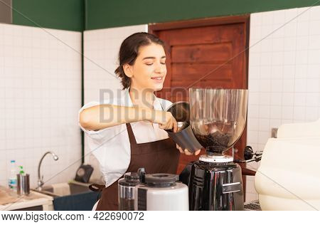 Beautiful Caucasian Barista Woman Scooping Coffee Beans From Coffee Equipment Into Coffee Bean Grind
