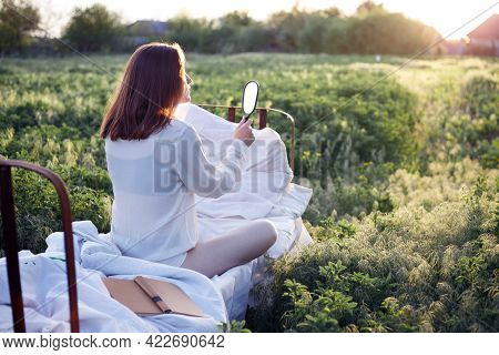 Girl In Bed Among The Fields At Sunset