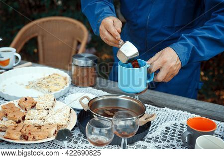 Man Pouring Coffee Into A Cup. Lunch In The Garden